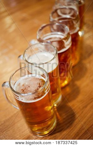 Several glass mugs of beer on wooden table, shallow dof.