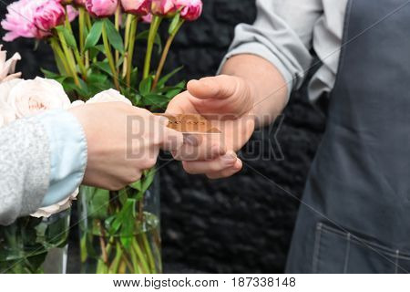 Florist receiving discount card from regular customer in flower shop, close up