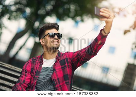 Young man is resting at the parktaking selfie