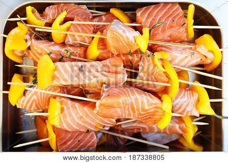 Shish kebab from raw salmon with slices of Bulgarian pepper on a tray. Outdoor barbecue