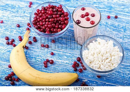 cranberry and banana smoothie in the glass lies next to a banana a plate with raw cranberries and a plate of cheese