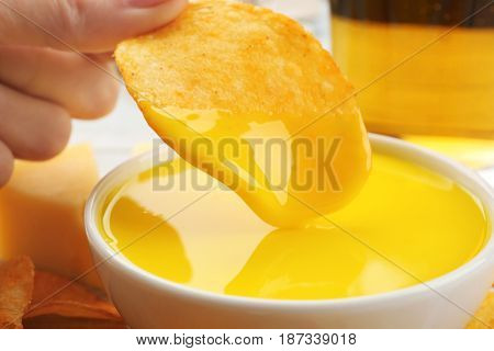 Dipping chips into bowl with creamy cheese sauce, close up