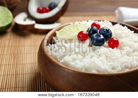 Coconut rice with berries and lime slice on bamboo mat