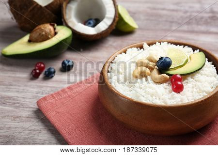 Coconut rice with berries, cashew nuts, avocado and lime slices on wooden table