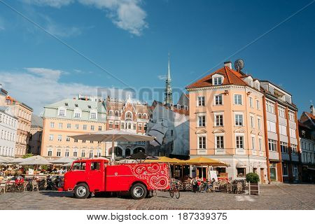 Riga, Latvia - July 1, 2016: Big Red Car Of Street Musicians Buskers Stands Near Cafe On The Dome Square In Sunny Summer Day With Blue Sky