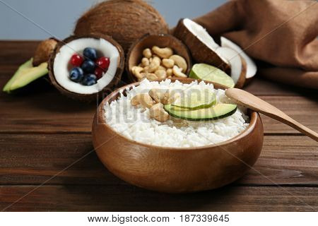 Coconut rice with cashew nuts, avocado and lime slices on wooden table