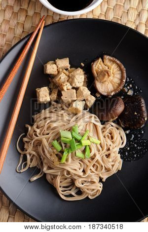 Traditional Japanese dish shiitake, soba, and tofu with soy sauce and green onion