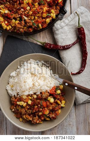 Chili con carne and red chili peppers with rice on a rustic table