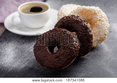 Cup of coffee and donuts with chocolate and white frosting