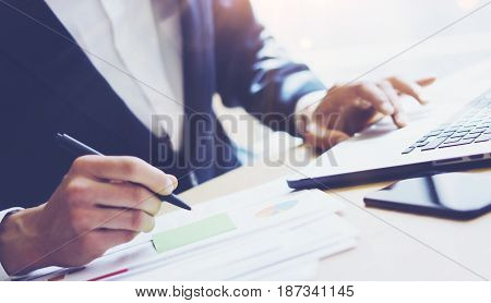 Businessman working at sunny office on laptop.Man pointing notebook keyboard and holding pen hand.Blurred background.Papaer documents on the table