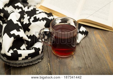 A cup of warm tea a warm blanket and a book on a wooden background