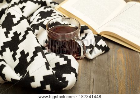 A cup of tea a warm blanket and a book on a wooden background
