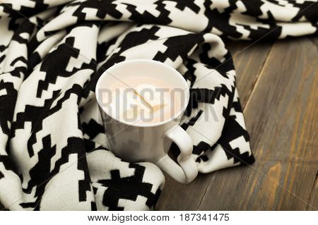 Hot chocolate marshmallow warm blanket on a wooden background