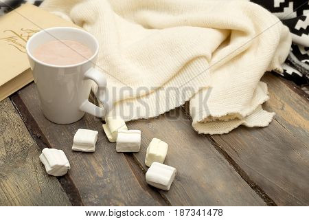 Cup of hot chocolate marshmallow book candle on a wooden background.