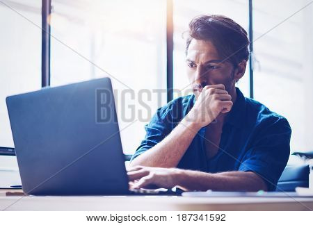 Young handsome banking finance analyst working at sunny office on laptop while sitting at wooden table.Businessman analyze stock reports.Blurred background, horizontal