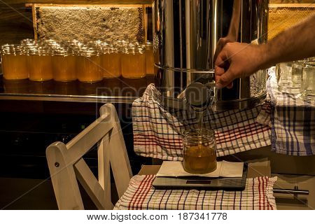 Beekeeper filling up the fresh new honey into glass jars