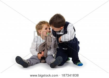 2 Little brothers wearing festive clothing sitting together on the floor toddler has plush animal (rabbit) and pacifier. Isolated on white background