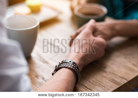Close up of male arm holding female hand with gentleness. Couple is drinking coffee while sitting at table