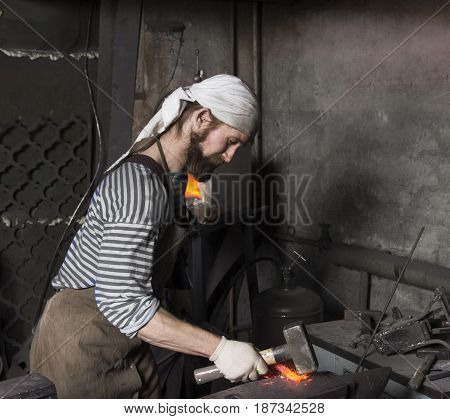 Senior blacksmith with brush handles the molten metal on the anvil in smithy