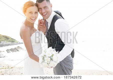 happy bride and groom on the beach at sunset