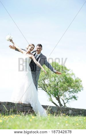 Bride and groom having fun walking on parapet