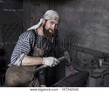 senior blacksmith forges detail. Blacksmith working outdoors. Master works on the anvil.