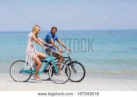 Side view of happy couple riding bicycles on shore at beach