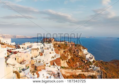 lanscape of Oia with people watching sunset, volcano caldera and Aegan sea, beautiful details of Santorini island, Greece