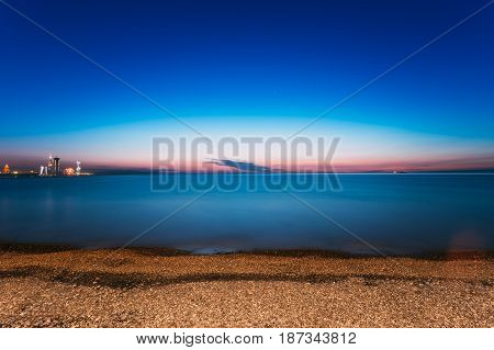 Batumi, Adjara, Georgia. Scene Of Resort Town At Sunset Or Sunrise. Bright Evening Sky. View From Sea Beach To Illuminated Cityscape With Modern Urban Architecture, Skyscrapers And Tower