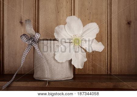 Stunning white clematis in a vase covered by a hessian bag with gingham ribbon to handle. Desaturation applied for country rustic effect.