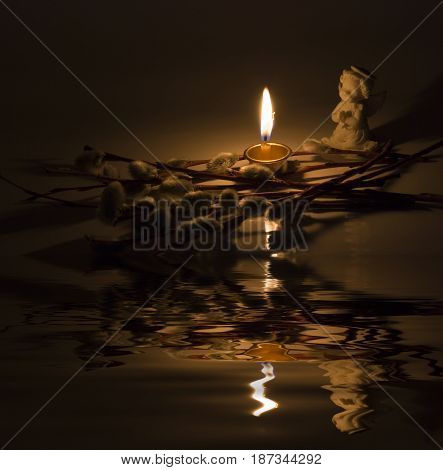 Angel burning candle and willow twigs reflected in the water surface with small waves