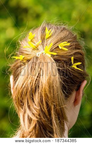 A Young woman with plait and yellow flowers in hair