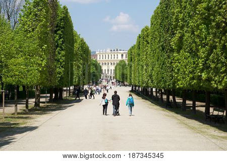 VIENNA, AUSTRIA - APR 30th, 2017: Public park in Schonbrunn Palace Schonbrunn Palace. It's a former imperial 1441-room Rococo summer residence of Sissi Empress Elisabeth of Austria in modern Wien. Tourist walking in the park.