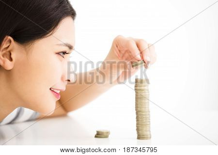young woman put coins to stack Saving money concept