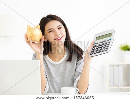 Young asian Woman showing Calculator and Piggybank