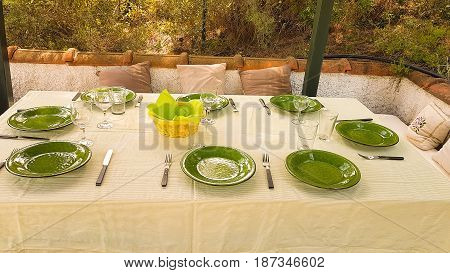 Green dishes on table ready for food to be served on a formal lunch time.