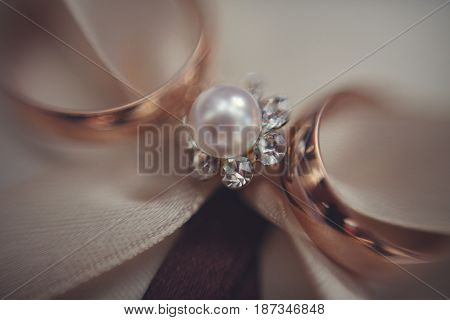 Blurred picture of wedding rings lying over the pearl brooch