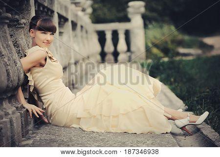 Woman in beige dress rests beneath stone pillars