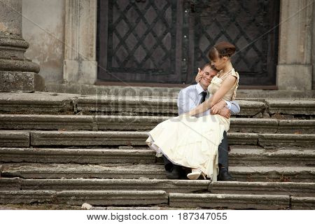 Lady Embraces Man's Head To Her Chest Sitting On The Stone Footsteps
