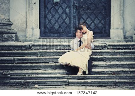 Tender Lady Sits On Groom's Knees While They Pose On Ruined Footsteps
