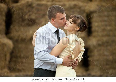 Man Kisses Lady In A Cheek Hugging Her Betwenn Haycocks