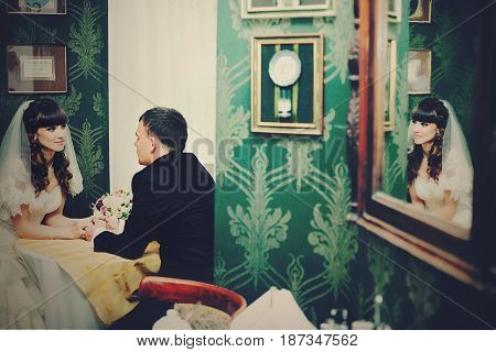 Stylish Wedding Couple Sits In The Green Restaurant Hall