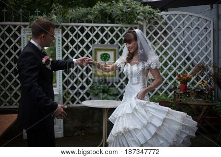 Groom Whirls A Bride Standing On The White Backyard