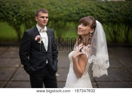 Smiling Bride Looks Up In The Sky While Groom Waits On The Background