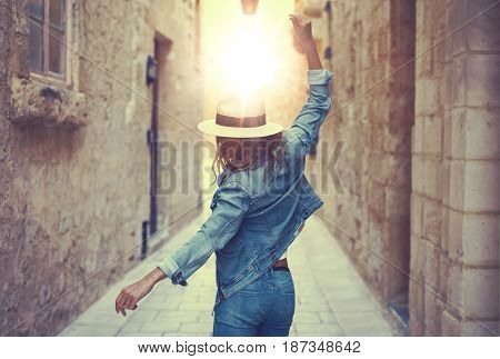 Young carefree woman in hat dancing at old narrow mediterranean street in sunset