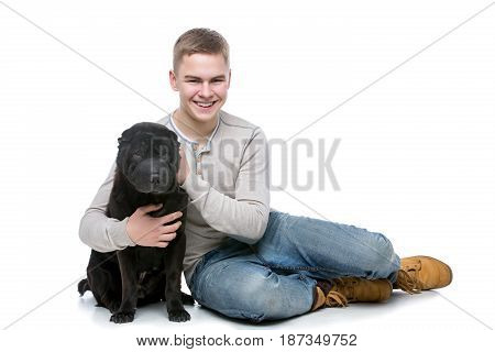 Handsome young man hugging black shar pei dog. Studio shot isolated on white background. Copy space.