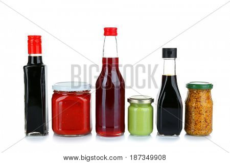 Glass jars and bottles of different sauces isolated on white