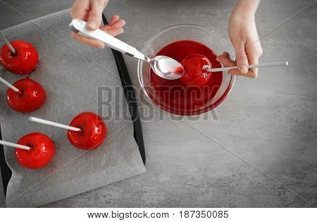 Woman glazing candy apple with caramel above glass bowl in kitchen