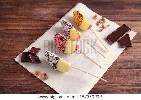 Parchment with candied apple wedges on wooden background