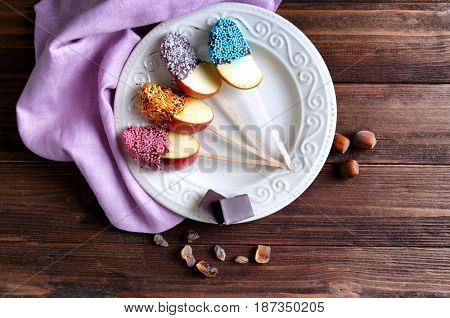 Plate with candied apple wedges on wooden background